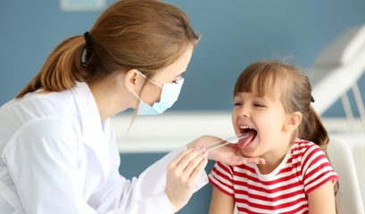Doctor,checking,little,girl's,throat,in,the,office