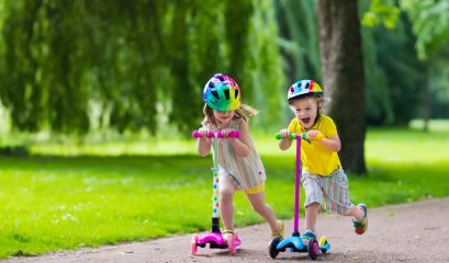 children,learn,to,ride,scooter,in,a,park,on,sunny