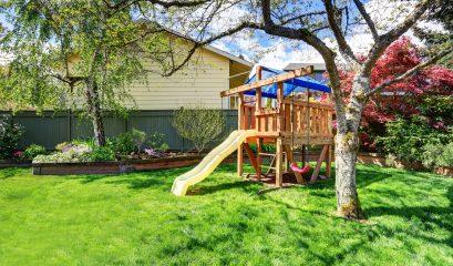 view,of,kids,playground,in,green,backyard,garden,with,birch